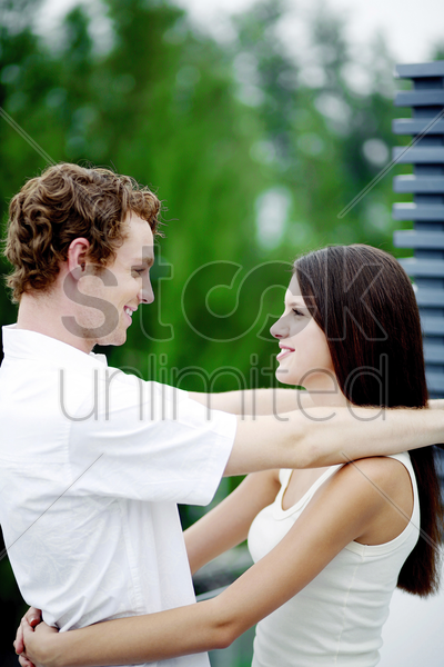 couple smiling while hugging each other stock photo