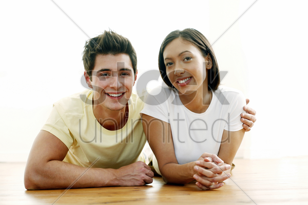 couple smiling while lying forward in the park stock photo