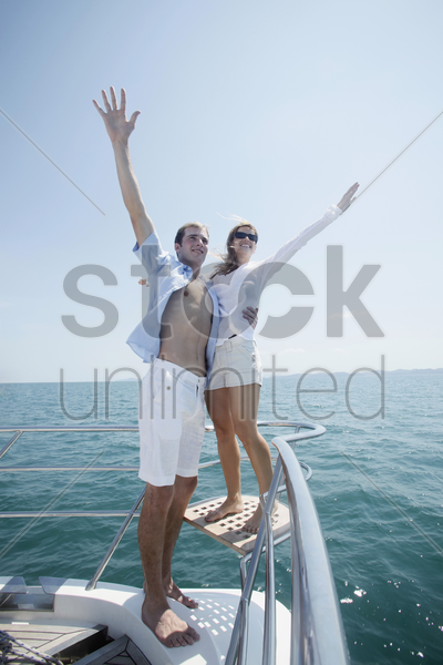 couple standing at the tip of the yacht with arms raised stock photo
