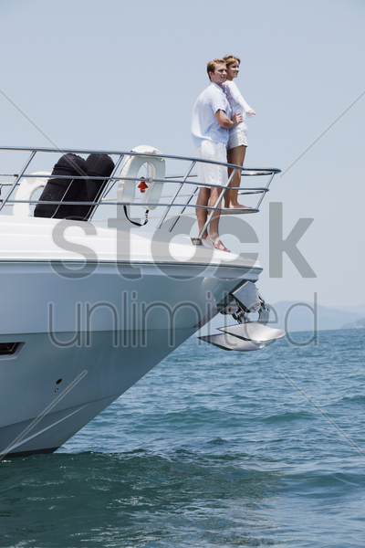couple standing at the tip of yacht stock photo