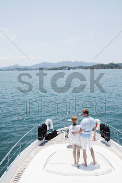couple standing on yacht deck stock photo
