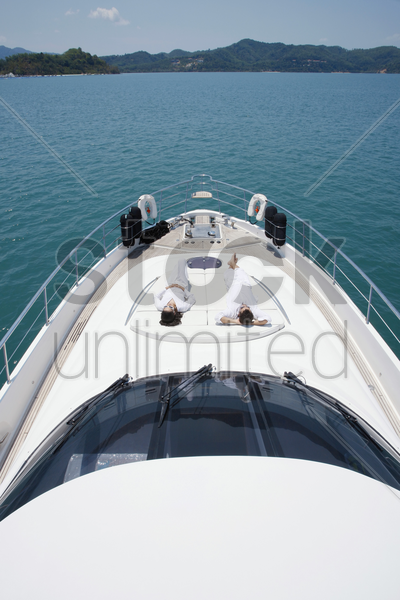couple sunbathing on yacht deck stock photo