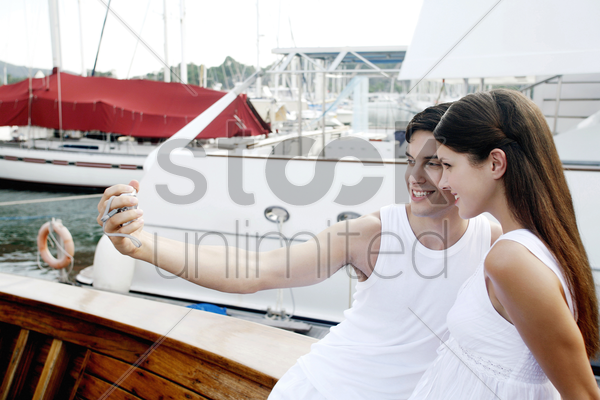 couple taking picture on a yacht stock photo