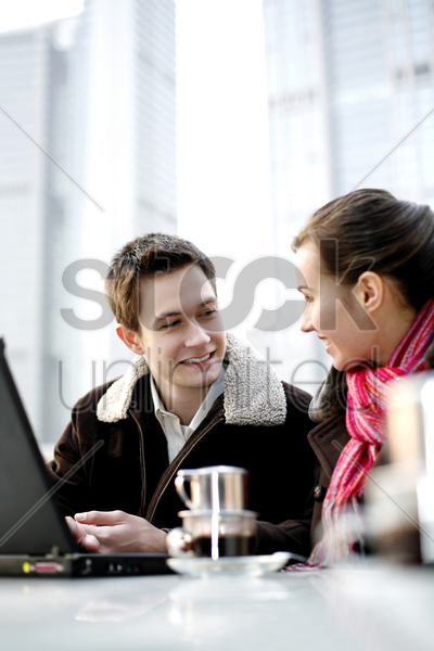 couple talking and using laptop in the cafe stock photo