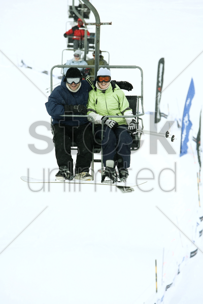 couple traveling on chair lift stock photo