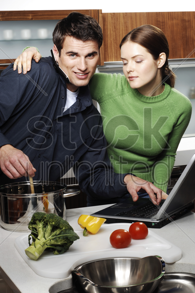 couple using laptop while cooking in the kitchen stock photo