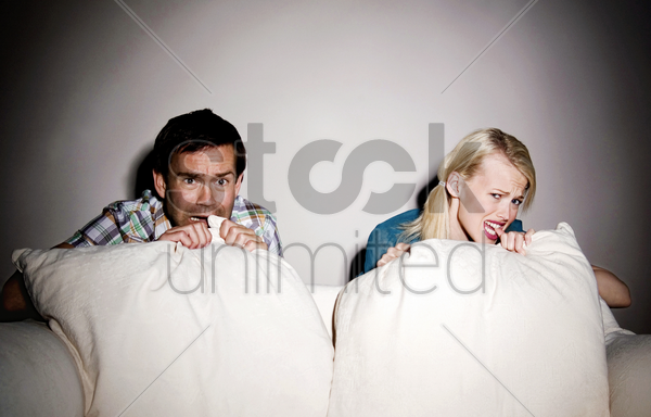 couple watching horror movie on the bed stock photo