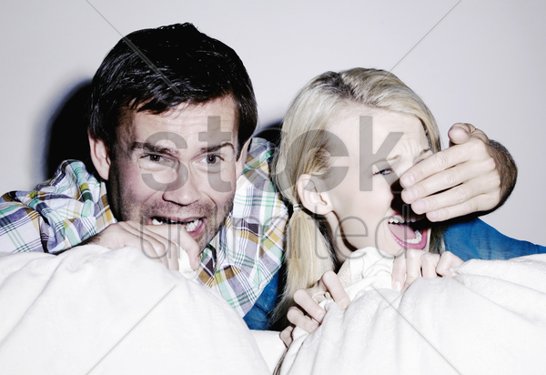 couple watching horror movie stock photo