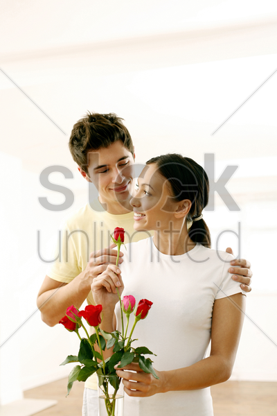 couple with a vase of roses stock photo