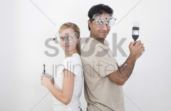couple with protection goggles and paint brush posing for the camera stock photo