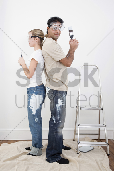 couple with protection goggles posing with paint brush stock photo