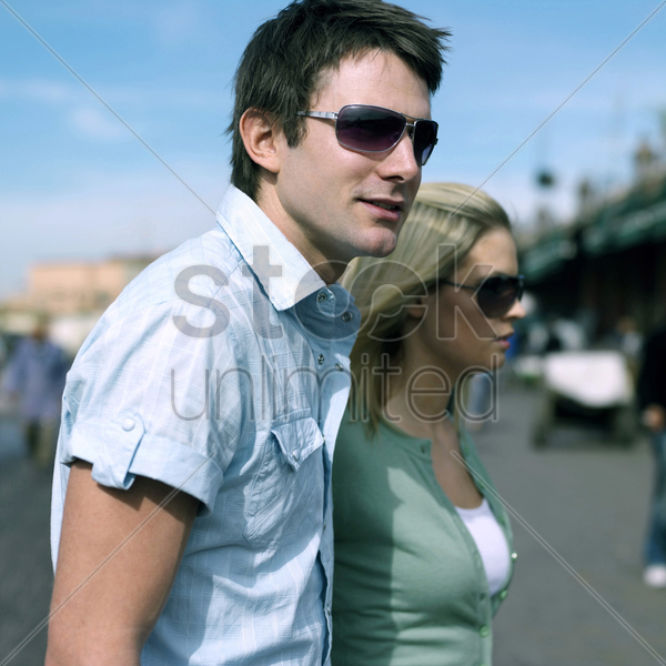 couple with sunglasses walking in morocco street stock photo