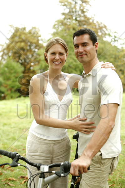 couple with their bicycle in the park stock photo