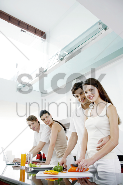 couples preparing food and using laptop in the kitchen stock photo