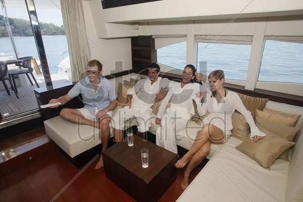 couples relaxing in yacht living room stock photo