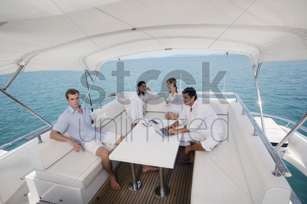 couples relaxing on yacht stock photo
