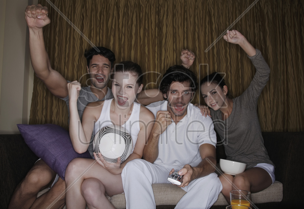couples watching soccer on tv together stock photo