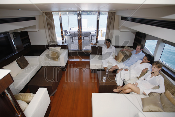 couples watching television in yacht living room stock photo