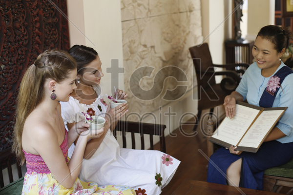 customer service representative explaining about choices of spa while women enjoy their tea stock photo