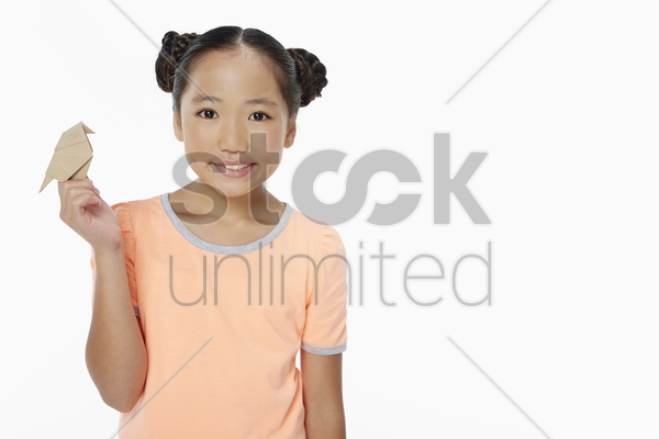 cute girl holding up a paper bird stock photo
