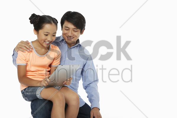 daughter sitting on father's lap, using digital tablet stock photo
