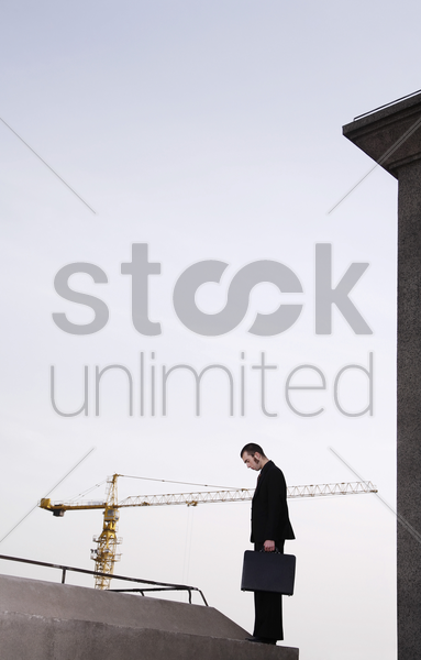 dejected businessman carrying a briefcase stock photo