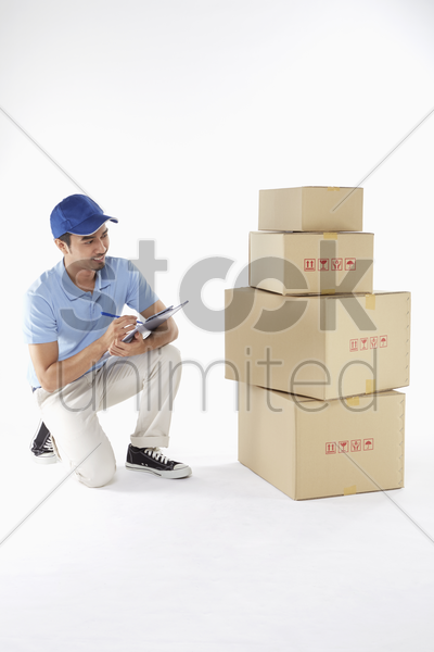 delivery man doing inventory on boxes stock photo