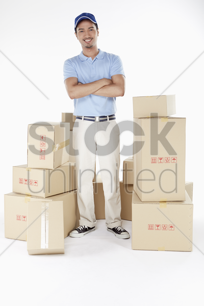 delivery man standing in the middle of cardboard boxes stock photo