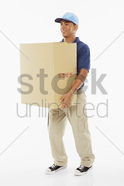 delivery person carrying a big cardboard box stock photo
