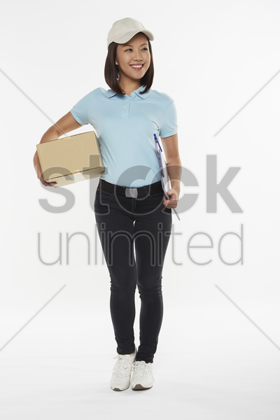delivery person carrying a box and clip file stock photo