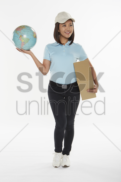 delivery person carrying a cardboard box and holding up a globe stock photo