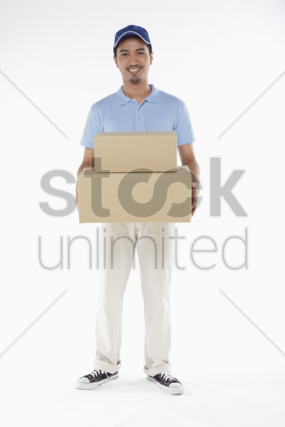 delivery person carrying a cardboard box stock photo