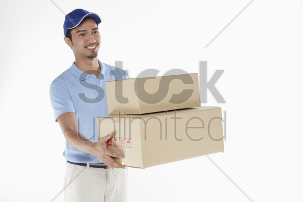 delivery person handing out cardboard boxes stock photo