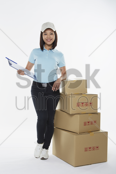 delivery person standing beside a stack of boxes stock photo