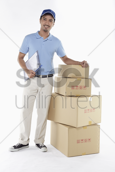 delivery person standing beside a stack of cardboard boxes stock photo