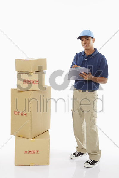 delivery person writing notes on clipboard stock photo