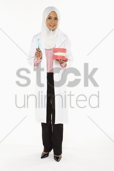 dentist holding a tooth brush and artificial dentures stock photo
