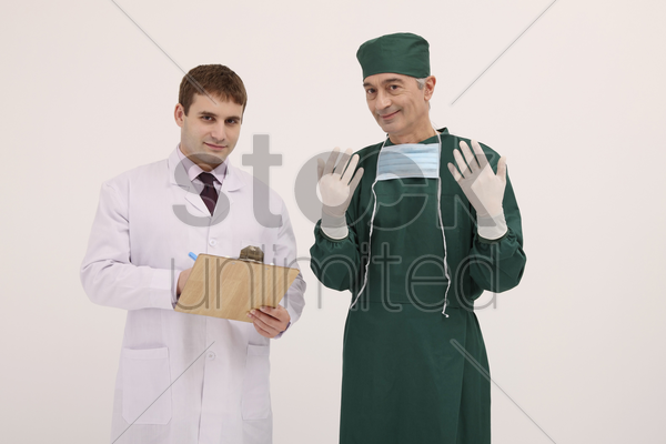 doctor holding clipboard, surgeon showing surgical gloves stock photo