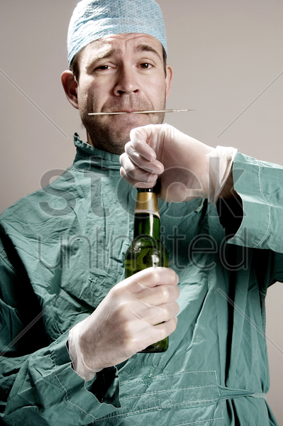 doctor opening a bottle of alcohol stock photo