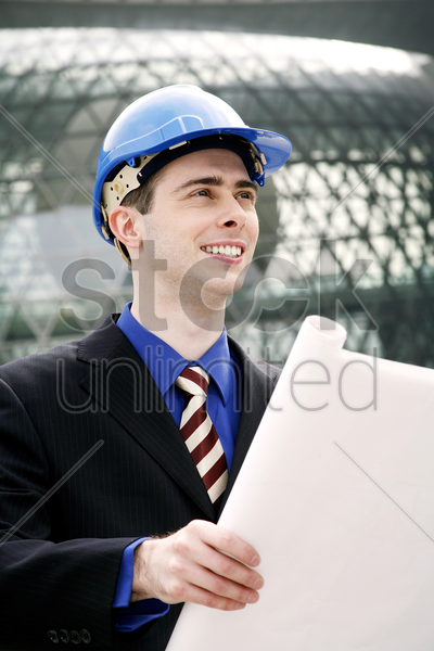 engineer with safety helmet holding a plan stock photo