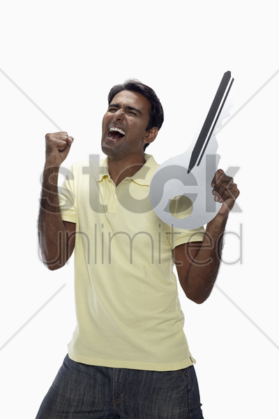 excited man holding a big key and cheering stock photo