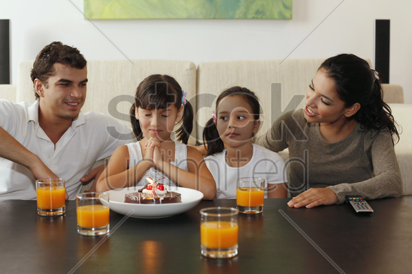 family celebrating girl's birthday stock photo