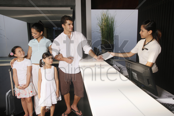 family checking into resort stock photo