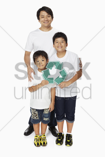 family of three smiling and holding up a recycle logo stock photo