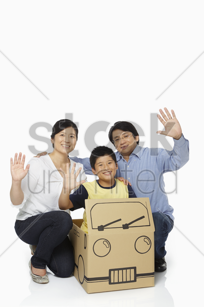 family of three waving at the camera stock photo