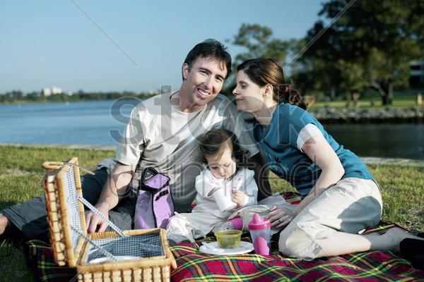 family picnicking in the park stock photo