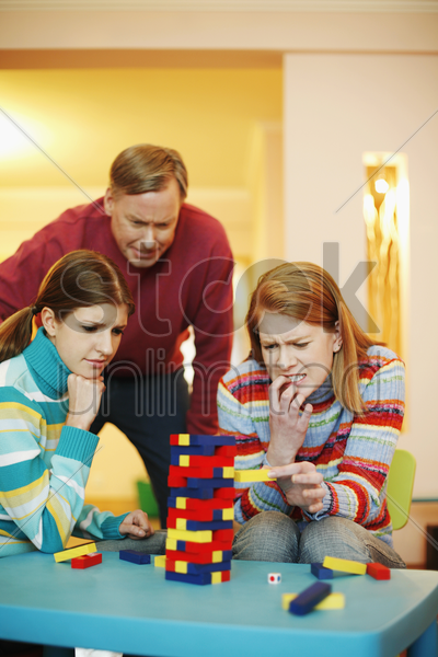 family playing block game at home stock photo