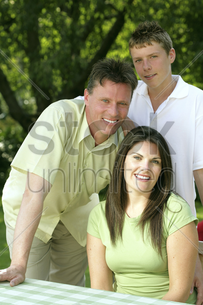 family posing at the picnic table stock photo