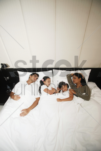 family sleeping together on bed stock photo