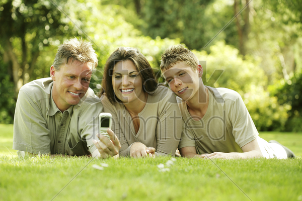 family taking picture with camera phone stock photo